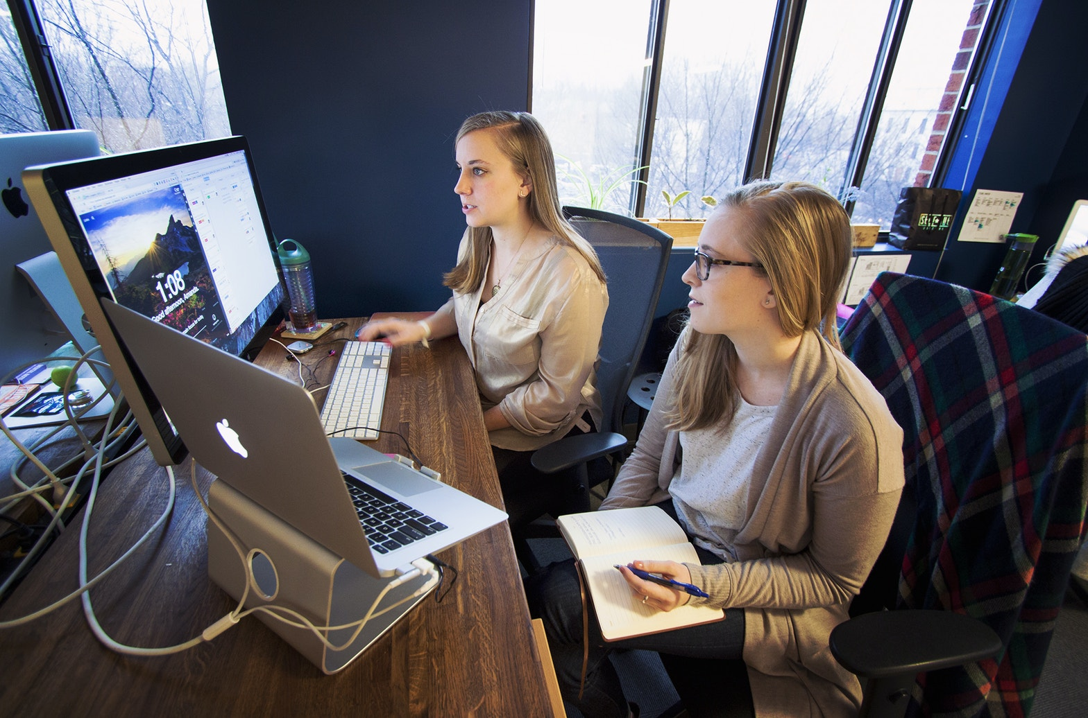 Amanda and Becca are PMs at Viget. They're sitting at a table reviewing project tasks.