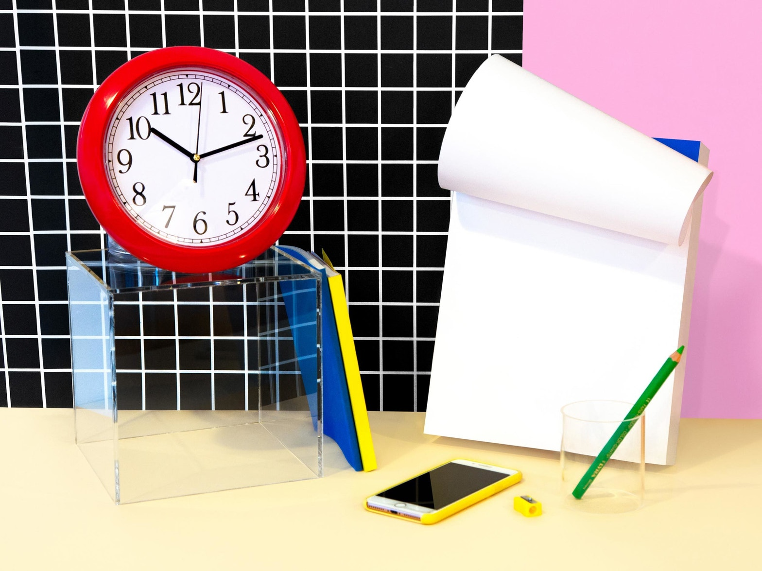 A colourful collection of stationery, a clock, and a smart phone